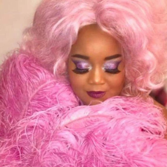 decorative image of a woman in pink with a pink wig
